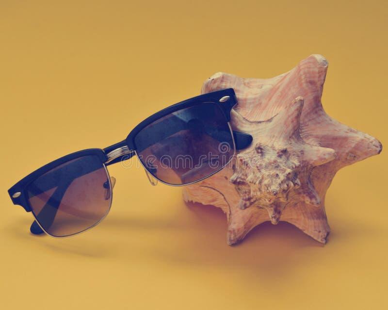 Lle coperture grandi ed occhiali da sole della mussola su un fondo giallo fotografie stock