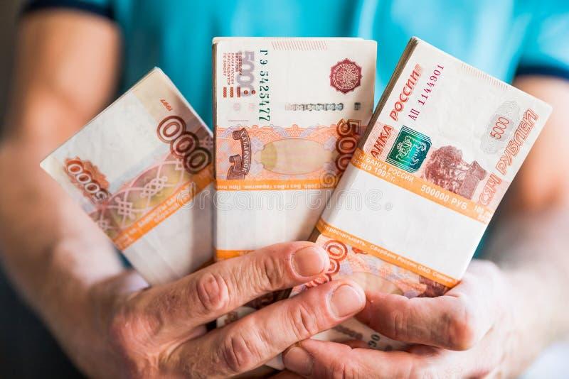 Lle denominazioni di cinque mila rubli russe Pacco delle banconote isolate in mano maschio 5000 rubli cinque mila contanti immagine stock