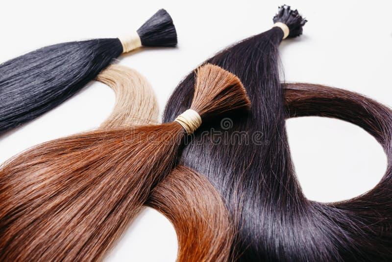 Lle estensioni dei capelli di tre colori su un fondo bianco fuoco selettivo del copyspace fotografia stock
