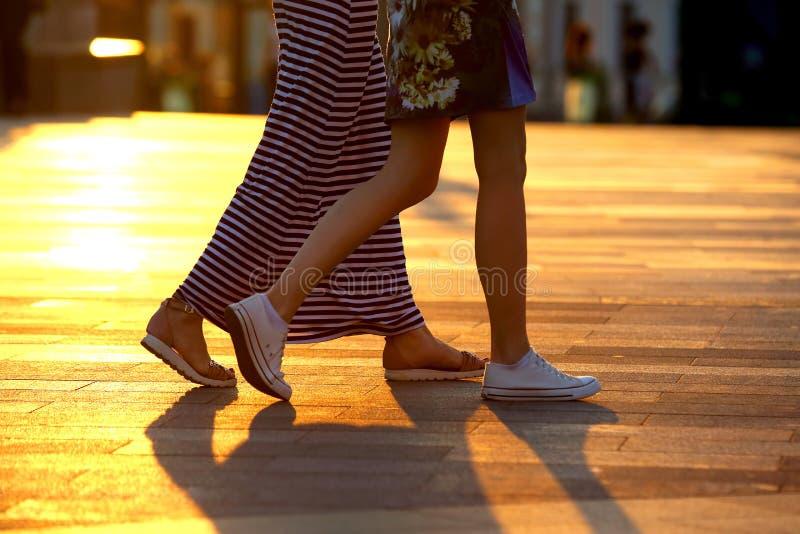 Lle gambe di due genti che camminano sui precedenti di luce solare fotografia stock libera da diritti
