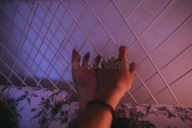Lle mani di due femmine che tengono il recinto del metallo di un letto immagine stock libera da diritti