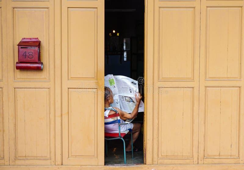 Lle notizie della lettura dell'uomo alla casa in George Town, Penang, Malesia immagini stock