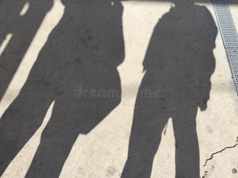 Lle ombre di un treno aspettante di due genti immagine stock libera da diritti