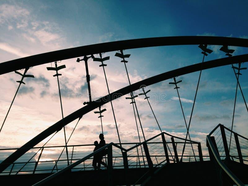 Lle siluette di due genti che camminano sul ponte di Frankston in Melbour immagine stock libera da diritti