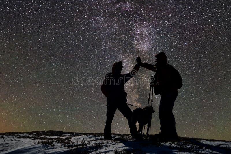 Lle siluette di due sciatori maschii adulti con il cane sopra la montagna innevata alla notte Cielo stellato scuro su fondo fotografia stock