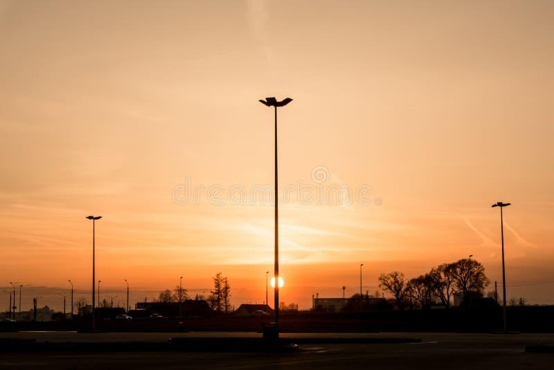 Lle siluette di tre pali della luce di illuminazione di via formano una prospettiva di un triangolo contro il tramonto sopra l'or immagine stock libera da diritti
