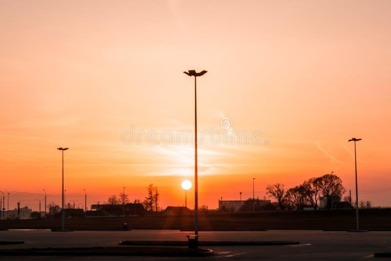 Lle siluette di tre pali della luce di illuminazione di via formano una prospettiva di un triangolo contro il tramonto sopra l'or fotografia stock