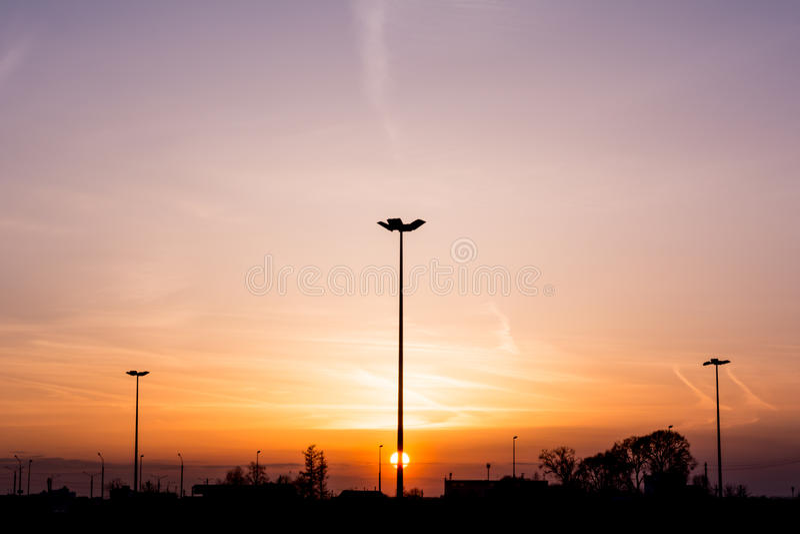 Lle siluette di tre pali della luce di illuminazione di via formano una prospettiva di un triangolo contro il tramonto sopra l'or immagine stock