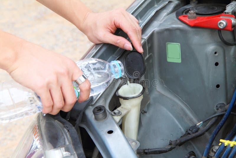 Llene el agua al líquido del limpiador en el tanque foto de archivo