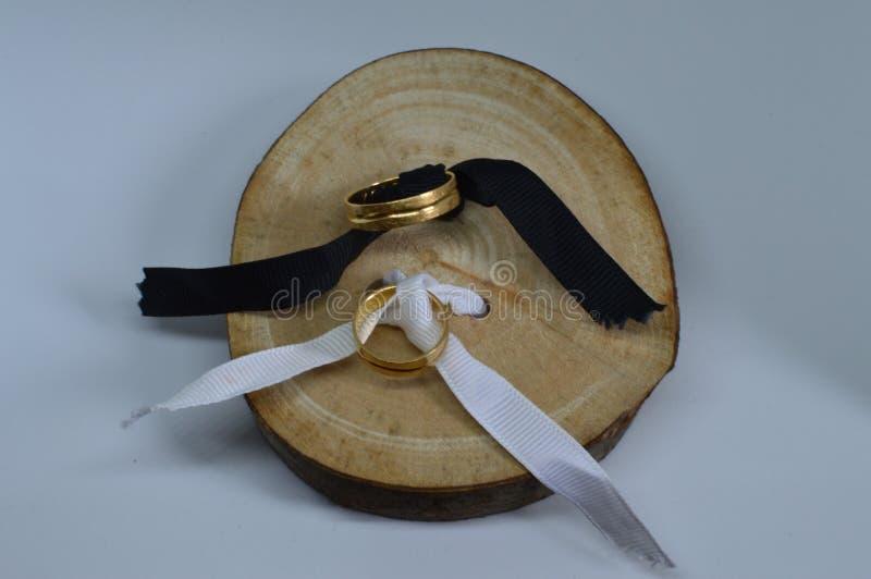 Lleva el tiro de las alianzas con los anillos de oro de la madera cortada Cepillo de dientes Bodas, vínculos, boda Fondos Textur  imagen de archivo