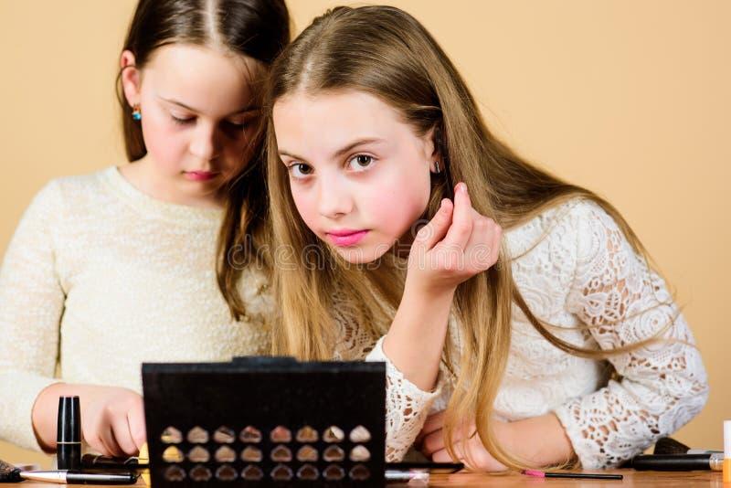 Lleva maquillaje la mirada natural Niñas lindas que hacen maquillaje para encontrar su mirada perfecta Pequeños niños adorables c imágenes de archivo libres de regalías