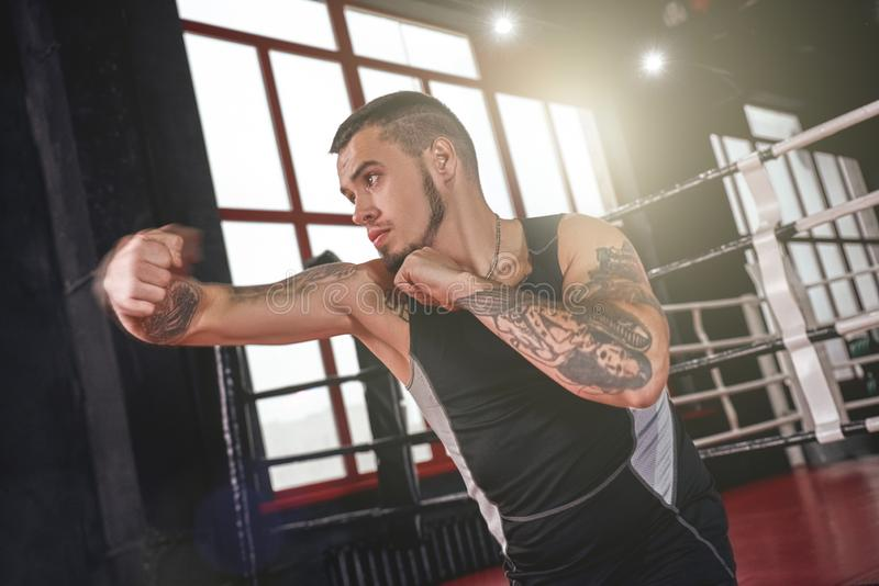 Llevado luchar Hombre fuerte en el boxeo de la ropa de los deportes con la sombra Gancho que lanza del atleta confiado en gimnasi imagen de archivo