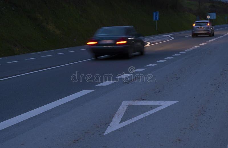 Llevan, los coches que corren en el camino en la noche fotografía de archivo libre de regalías