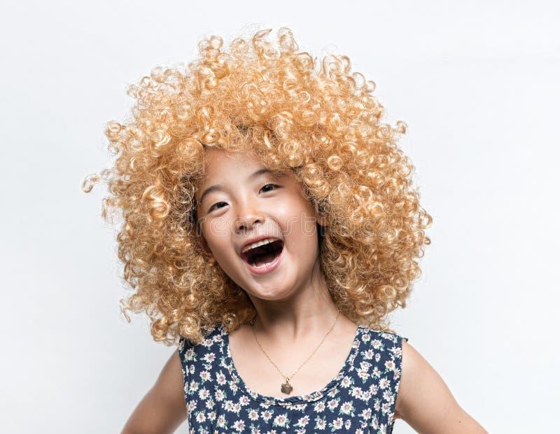 Llevar una peluca rubia y a una muchacha divertida del asiático de la expresión facial foto de archivo