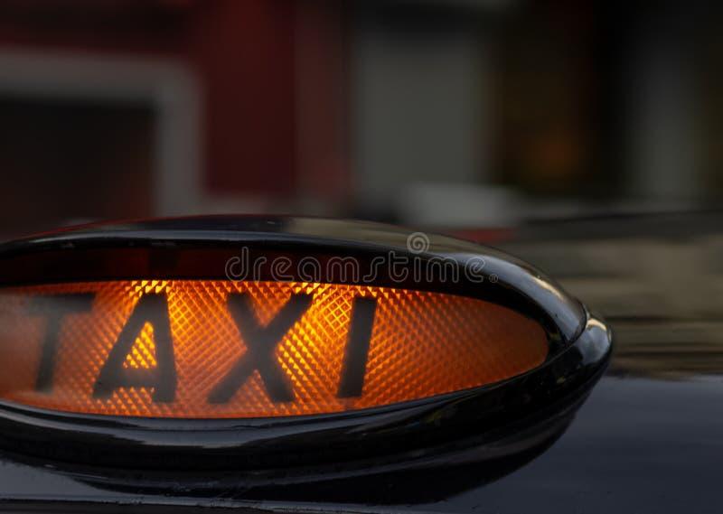 Lleve en taxi la muestra en el tejado de un coche en la noche foto de archivo libre de regalías