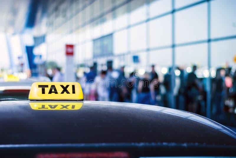 Lleve en taxi a los pasajeros de la llegada del coche que esperan delante de la puerta del aeropuerto foto de archivo libre de regalías