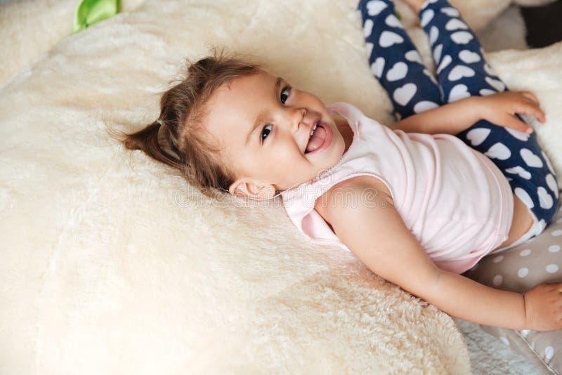 Llittle逗人喜爱的儿童女孩在床上说谎户内 库存照片