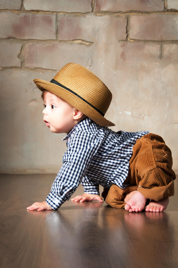 Llittle boy in retro hat and corduroy trousers learning to crawl on floor on all fours stock photos