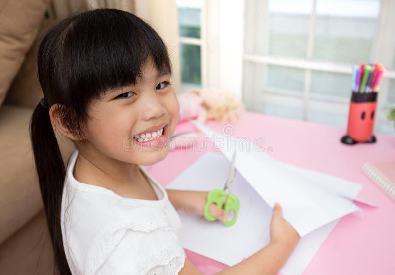 Llittle dziewczyna czuje szczęśliwego robi tnącego papier obraz royalty free