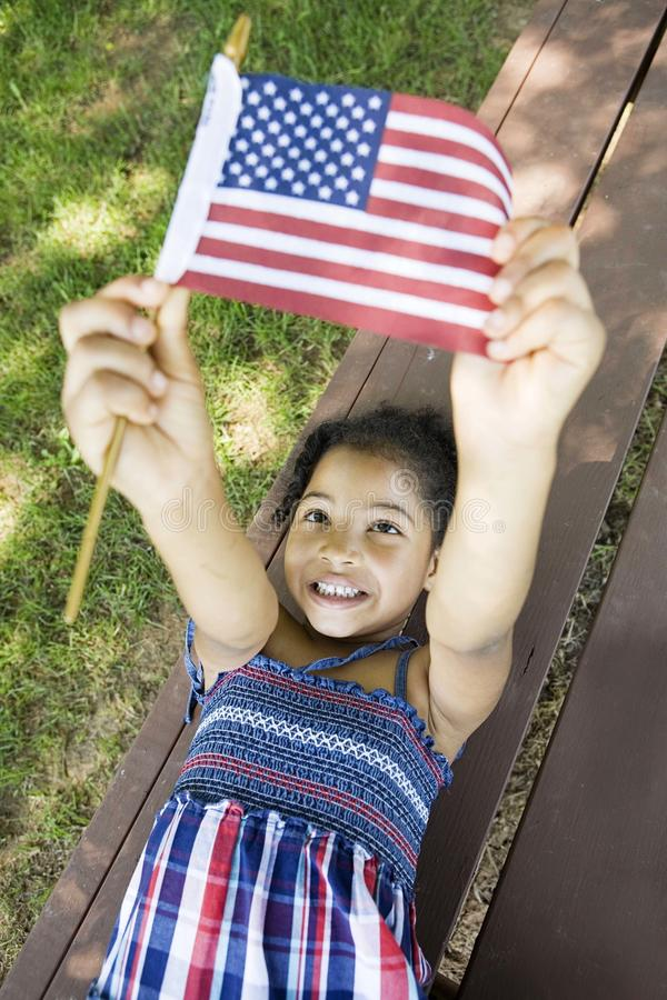 Llittle girl holding American flag. Young girl laying on a picnic table, at the park, holding up an American Flag stock image