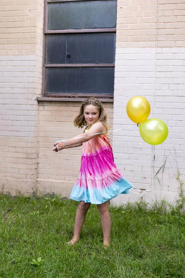 Llittle girl in rainbow coloured dress and bare feet swinging two balloons stock images