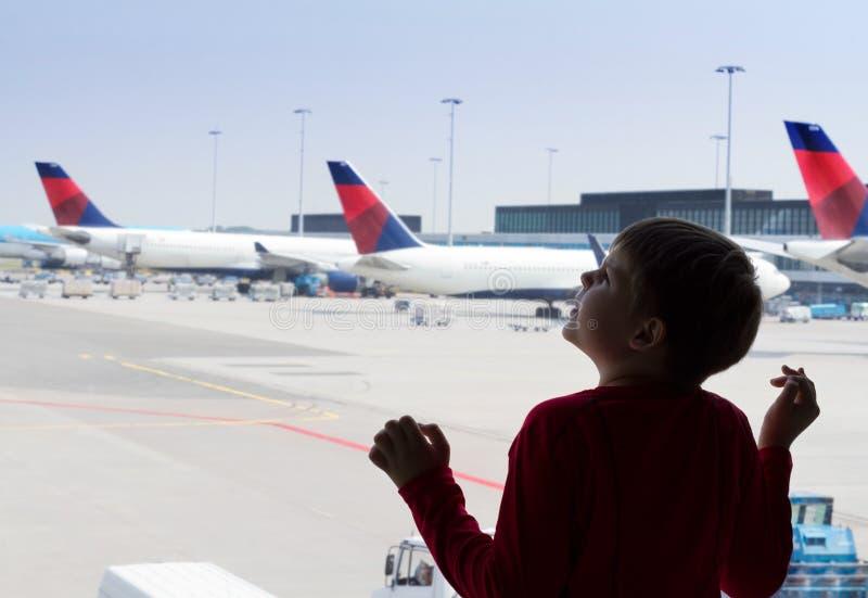 Llittle Junge, der den Himmel im Flughafen betrachtet stockbilder