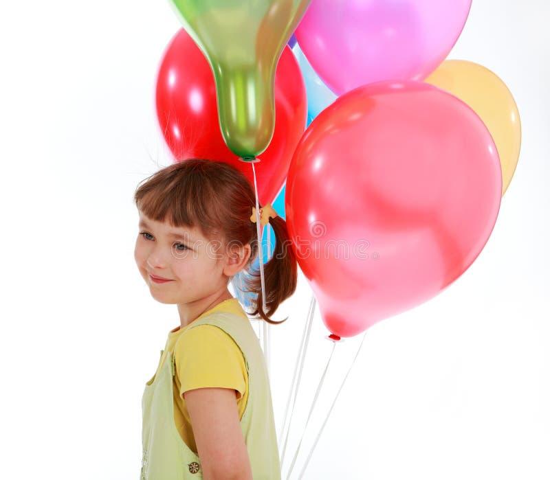 Llittle Mädchen, das bunte Ballone anhält lizenzfreie stockfotos