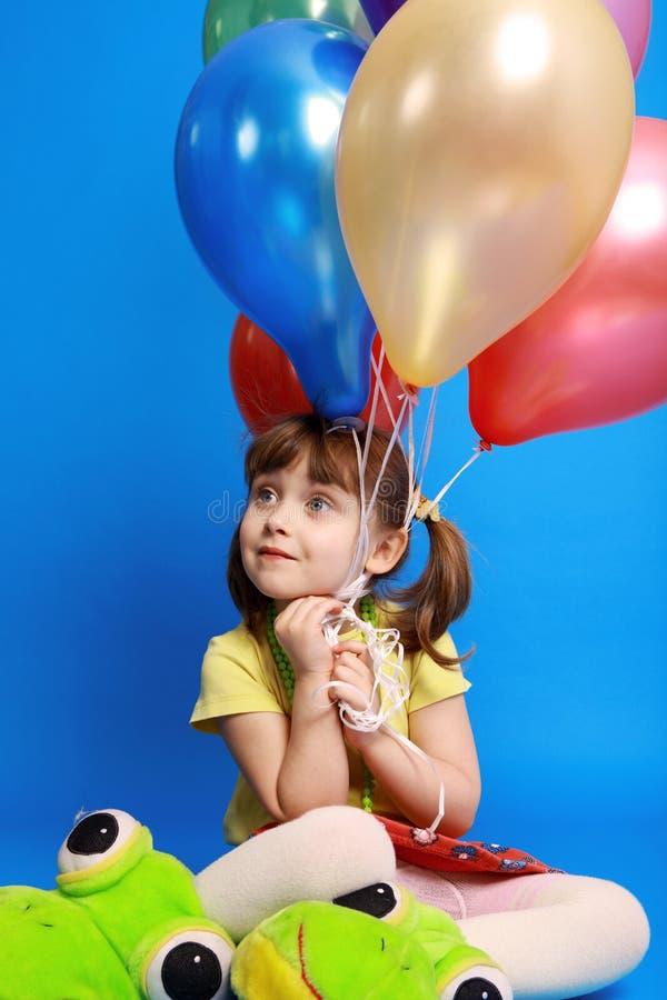 Llittle Mädchen, das bunte Ballone anhält stockfotografie