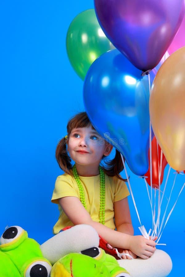 Llittle Mädchen, das bunte Ballone anhält lizenzfreies stockfoto