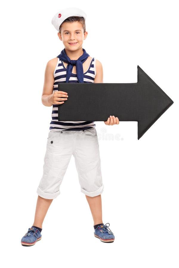 Llittle pojke i sjömandräkten som rymmer en stor svart pil arkivfoto