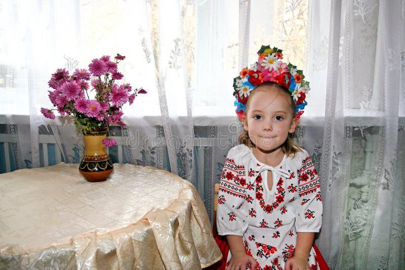 llittleflickan i ukrainsk nationell dräkt med kransen på hennes huvud sitter nära tabellen royaltyfri bild