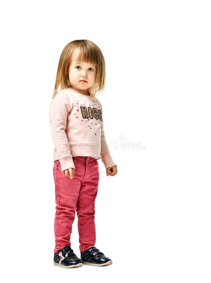Llittlemeisje in jeans op witte achtergrond wordt geïsoleerd die stock foto