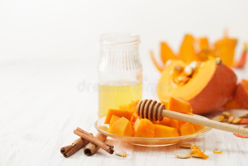 Lloviznado con la calabaza de la miel corte en pedazos en el plato, la miel y el canela fotografía de archivo libre de regalías