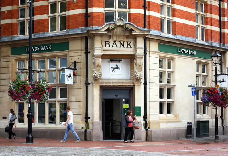 Lloyds Bank. Reading, England - August 28th, 2014: A woman exits the Reading branch of Lloyds Bank as other people pass by. The UK Treasury owns 25% of Lloyds royalty free stock photo