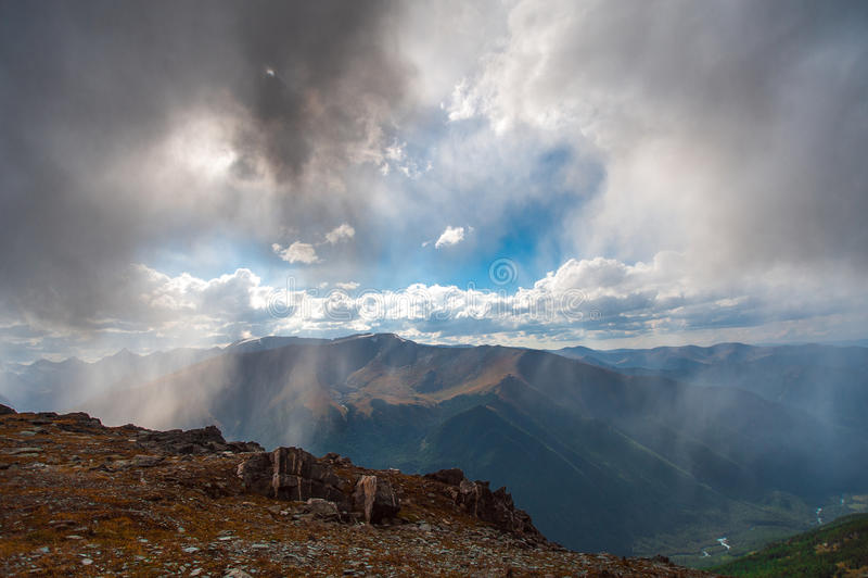 Llueva en las montañas con un brillo del cielo azul fotos de archivo