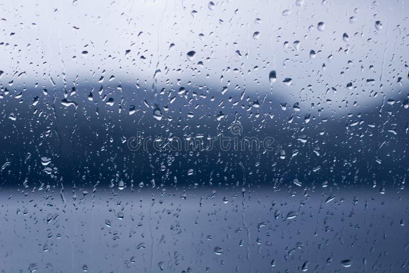 Llueva los descensos en descensos de una ventana o del agua en el fondo de cristal imagenes de archivo