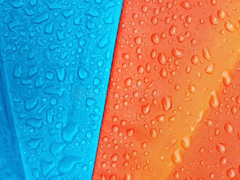 Llueva los descensos en el paraguas, fondo del color fotos de archivo libres de regalías