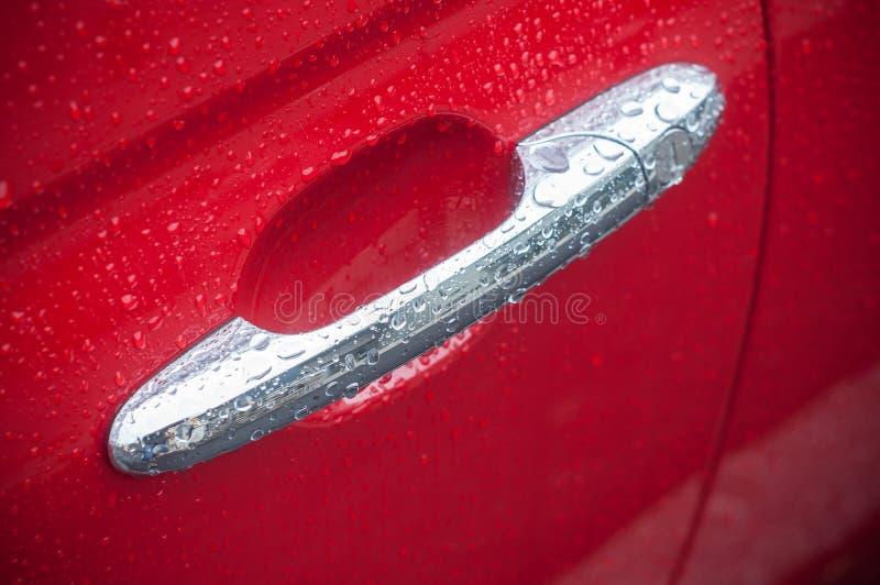 Llueva los descensos en la manija metálica en el coche rojo imagen de archivo