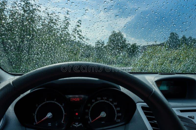 Llueva los descensos en un parabrisas con el volante de un coche fotos de archivo libres de regalías