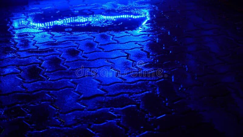 Lluvia en la calle de la noche Reflejo de luz azul en charco imagen de archivo