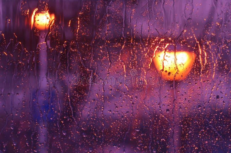 Lluvia púrpura en el vidrio de la ventana fotos de archivo libres de regalías