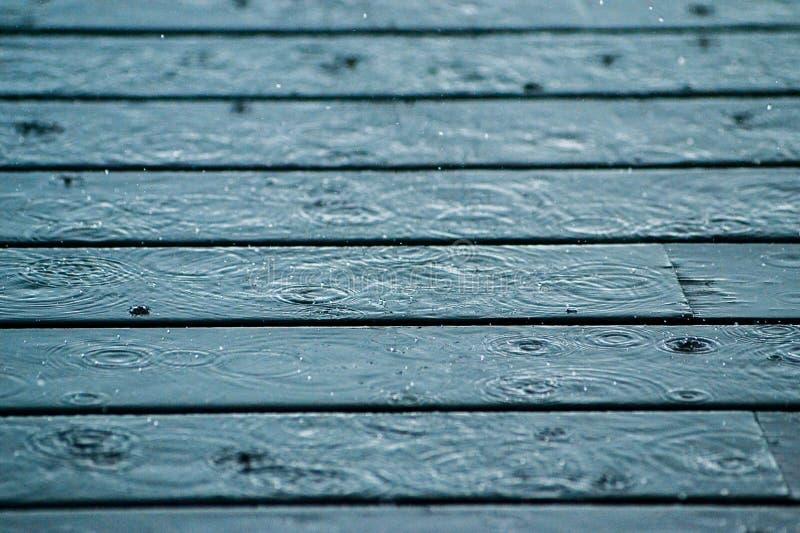Lluvia que cae en cubierta de madera foto de archivo