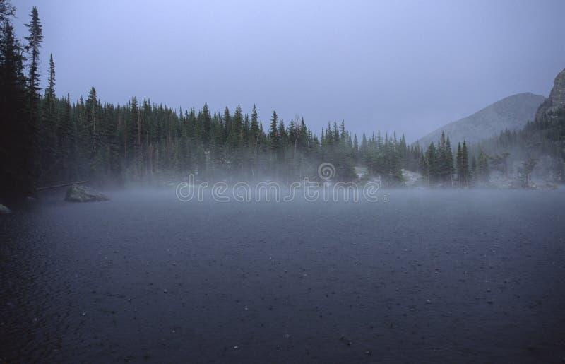 Lluvia sobre el lago alpestre en montañas rocosas fotos de archivo libres de regalías