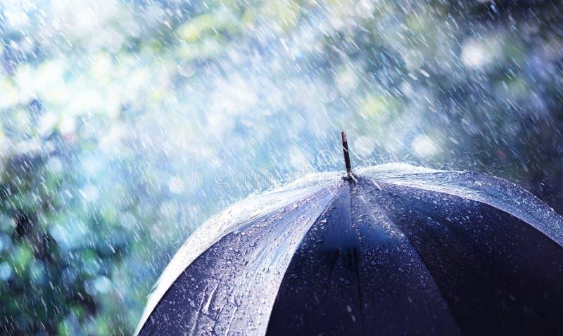 Lluvia y viento en el paraguas negro fotos de archivo