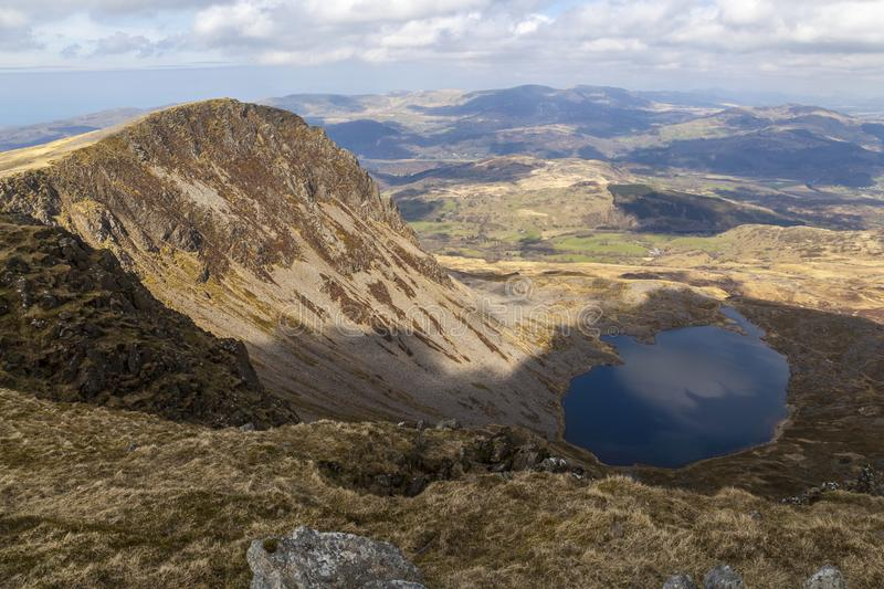 Llyn Y Gadair View. Looking down from the summit of Cadair Idris is the lake of Llyn Y Gadair with the summit of Cyfrwy to the left royalty free stock image