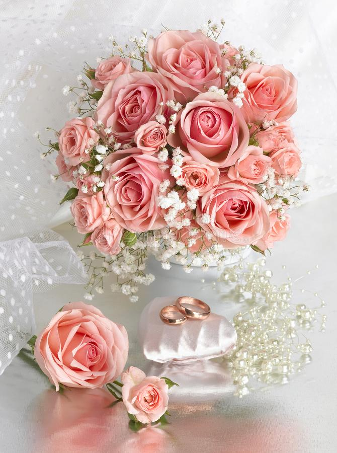 Wedding bouquet of pink roses. Wedding rings royalty free stock images