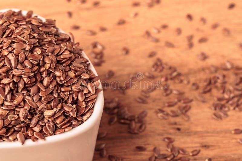 Lnów ziaren linseed w pucharze na drewnianym stole zdjęcie stock