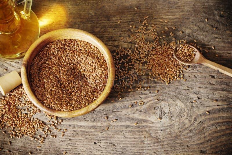 Lnów ziarna i linseed olej w szklanym dzbanku na drewnianym stole obraz royalty free
