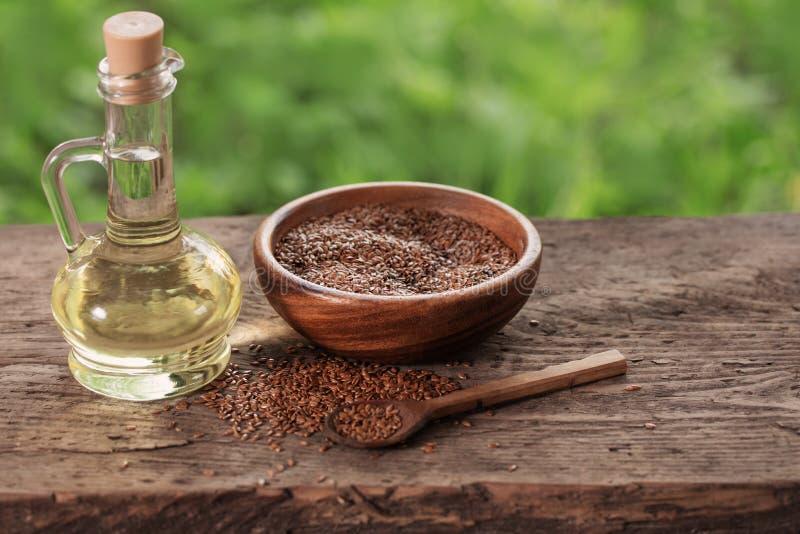 Lnów ziarna i linseed olej w szklanym dzbanku na drewnianym stole zdjęcia royalty free