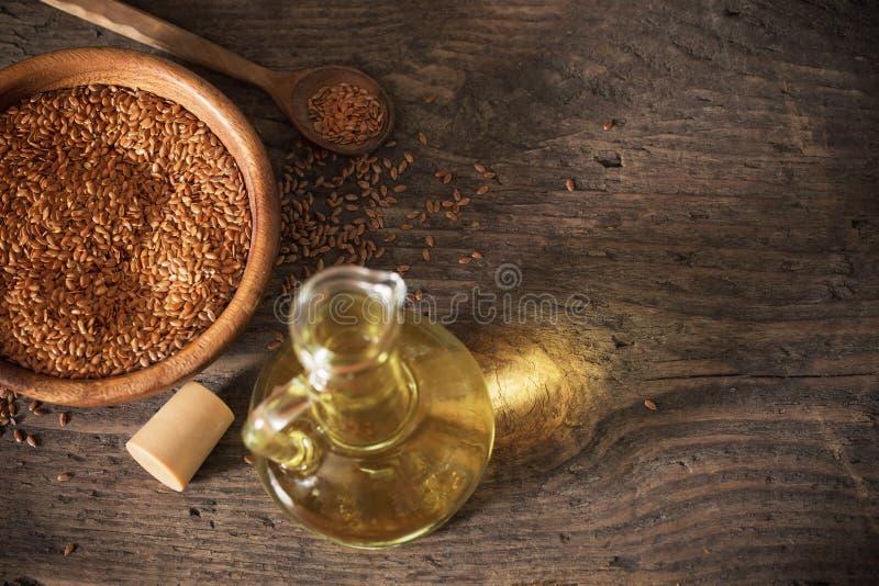 Lnów ziarna i linseed olej w szklanym dzbanku na drewnianym stole zdjęcie royalty free